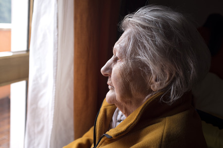 portrait of sad lonely pensive old senior woman looking in a window 版權商用圖片 - 60320213