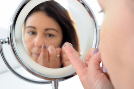 short sighted 50-year-old woman with contact lens balanced on the end of her finger in front of mirror