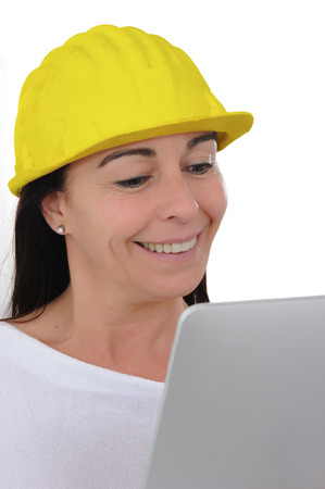 beautiful fifty year old woman smiling with yellow crash helmet and tablet