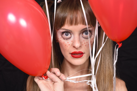 Portrait of a halloween horror doll woman looking through balloons-party