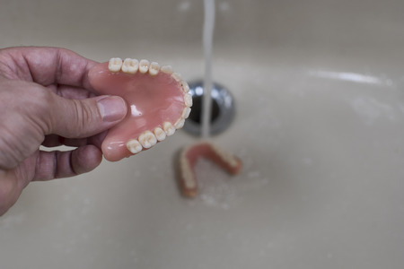 denture cleaning in the sink with running water