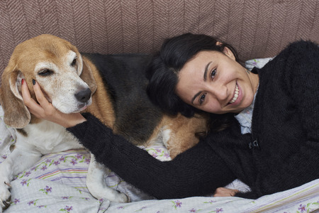 young woman and her Beagle dog, in bed