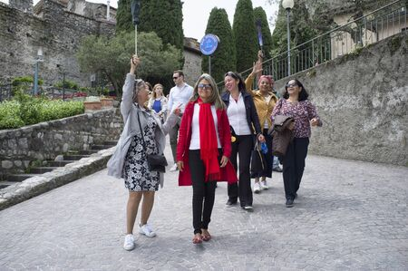18 may 2019 - Sirmione, Lake Garda, Italy - Happy group of Brazilian tourist, walking with a tour guide