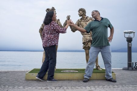 28 may 2019 - Lazise, lake Garda, Italy - happy couple of Brazilian tourists imitate the pose of the statue of Juliet and Romeo