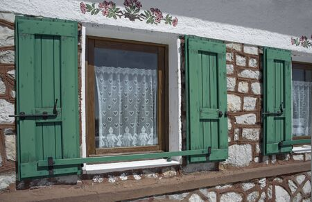 green wooden windows in a typical Italian mountain house