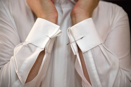 Groom uses safety pins instead of the forgotten cufflinks before the ceremony