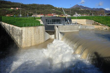 hydroelectric power plant, hydropower system, uses a dam to store river water in a reservoir. Water released from the reservoir flows through a turbine, spinning it, which in turn activates a generator to produce electricity 版權商用圖片