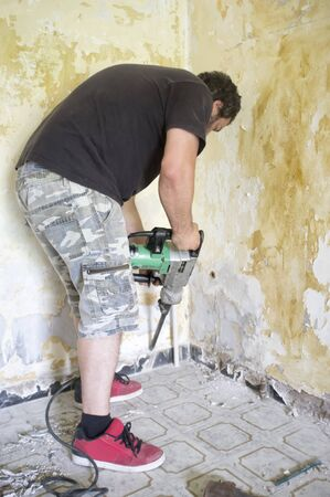 bearded man with demolition hammer works inside a house 版權商用圖片