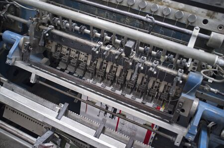 detail of industrial bookbindery machine in action