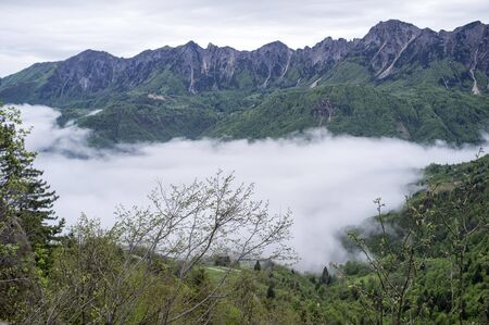 mountains with clouds covering the valley below