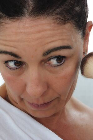 close-up of mature woman puts the fard on her cheeks Archivio Fotografico