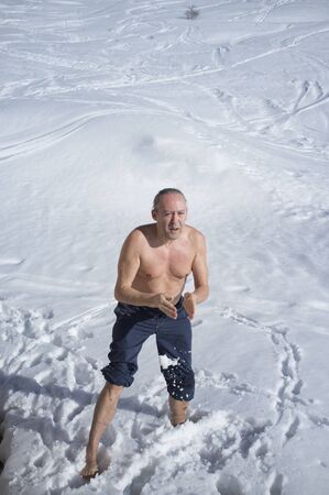 adult man practicing cryotherapy, in the snow. Cryotherapy is a pain treatment that uses a method of localized freezing temperatures to deaden an irritated nerve
