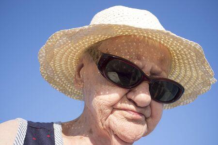 portrait of elderly with hat and dark glasses on a blue background Reklamní fotografie