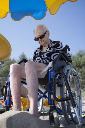 old woman in a wheelchair dozing on the beach with your feet in the sand Reklamní fotografie