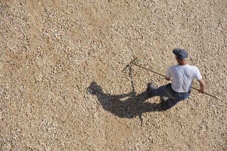 Man doing work raking the ground