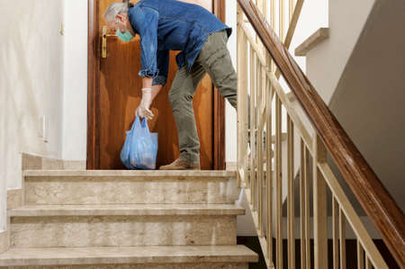 home delivering some groceries at quarantine time because of coronavirus infection COVID-19. Man with protective gloves, leaves the bag grocer on the doorstep