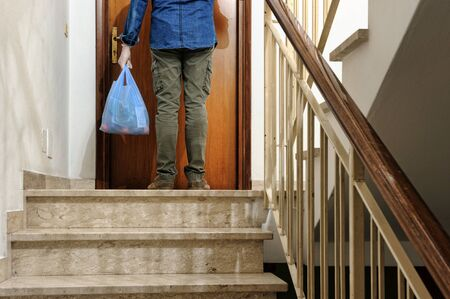 home delivering some groceries at quarantine time because of coronavirus infection COVID-19. Man with protective gloves, delivery of groceries at home