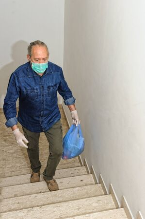 home delivering some groceries at quarantine time because of coronavirus infection COVID-19. Man with protective gloves, climbing stairs holding a grocery bag 版權商用圖片