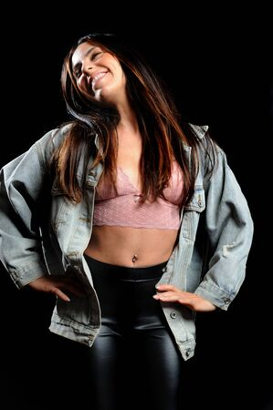 beautiful girl with denim jacket, pink top and black tight pants, and straight hair, on a black background