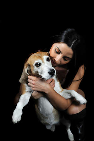sexy girl with her Beagle dog on the black background
