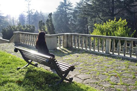 lonely woman in a park sitting on a bench in the cold winter light