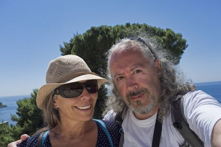 middle-aged couple on vacation at the beach makes a selfie 版權商用圖片