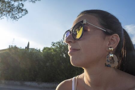 portrait of pensive girl with sunglasses, in the last rays of the setting sun