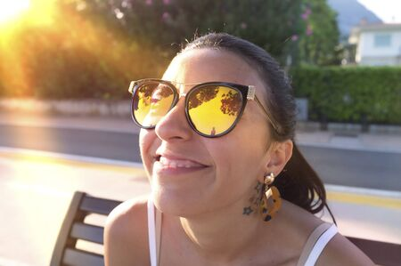 portrait of smiling girl with sunglasses, in the last rays of the setting sun