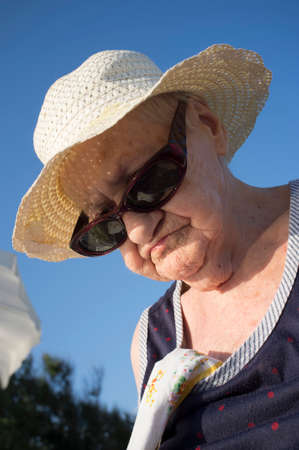 portrait of elderly with hat and dark glasses on a blue background 版權商用圖片
