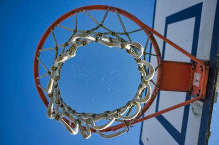 abandoned basketball basket, seen below, with a spider web in the middle
