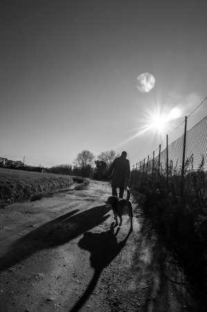 black and white image of a man, taken from behind walking followed by a dog, in backlight