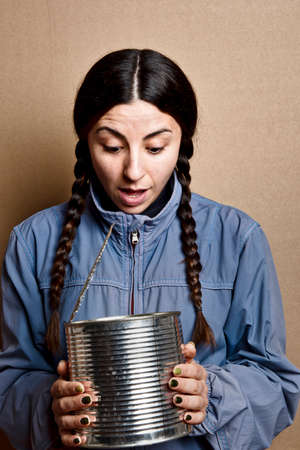 girl with no make up, pigtails and blue jacket, looks into a tin can, with wonder