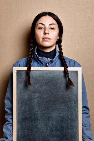 girl without make up holding a blackboard, and blue jacket, with the same hairstyle as Greta Thunberg, studio shot on brown cardboard background