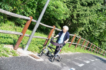 Handicapped senior lady with a walking disability pushing her walker on a bike path