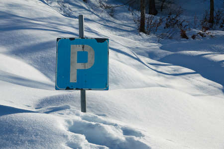 parking road sign submerged in huge snow drifts on mountains roads, after a heavy snowfall