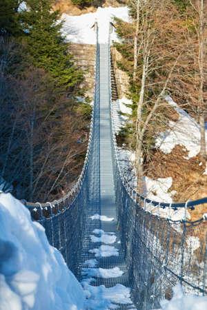 Tibetan suspension metal bridge in Valli del Pasubio, Italy, in winter Standard-Bild