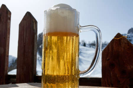 Cold beer and winter time in the Alps. Mountains landscape