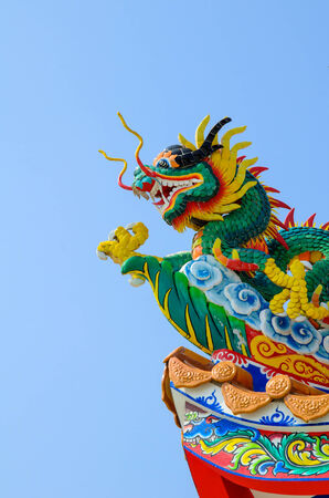 Chinese style dragon statue on roof against blue sky photo