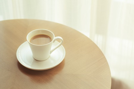 Coffee cup on wood table with vintage blur filter effect photo