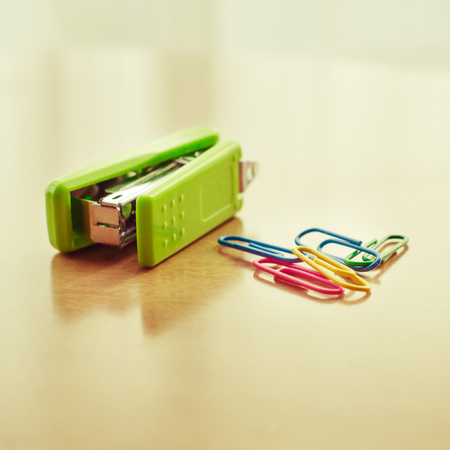 Green stapler and paper clip on table with blur vintage filter photo