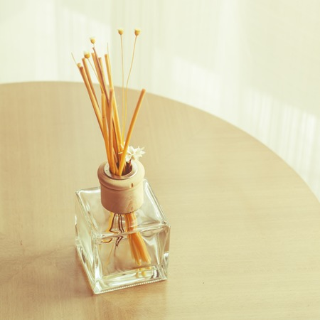 Aroma bottle glass and wooden sticks on the table with vintage filter photo