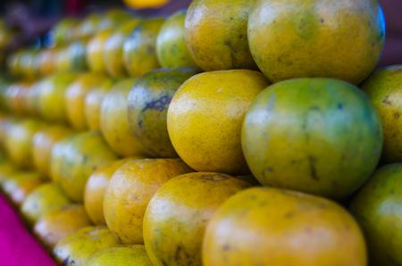 citrus reticulata: Depth of field close up focus a lots of orange on stack at market place,(Citrus reticulata, Tangerine)