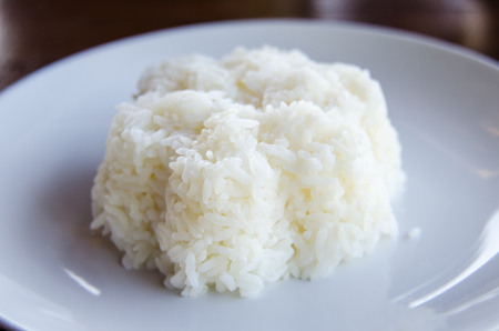 cooked rice: Cooked rice in white dish on old wooden table.