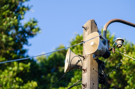 Speaker horn on electric pole against blue sky and green tree