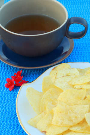 Cornflakes with hot tea, blue table, red flower  photo