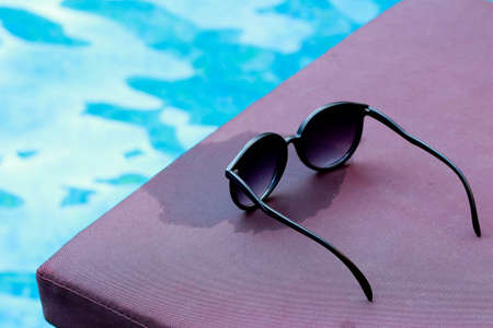 Sunglasses by the swimming pool  Stock Photo