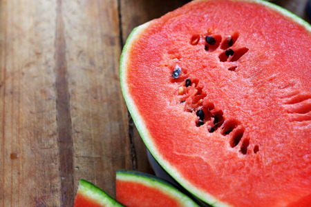 Watermelon fruit sliced pieces on the wooden floor.