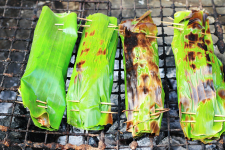 Sticky rice wrapped in banana leaves grill photo
