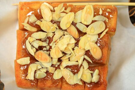 Toast bread topped with honey and almond. Stock Photo