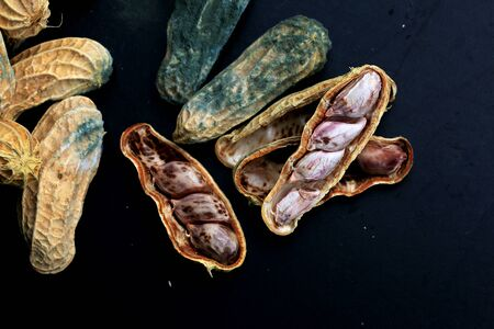 moldy: heap of moldy peanuts on a black background Stock Photo